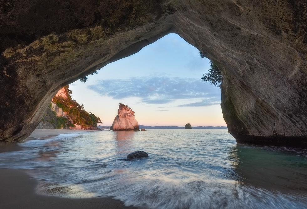 La enorme bóveda de esta cueva crea un rincón realmente pintoresco en la península de Coromandel. Se trata de una caverna con una arcada gigante, que pasa a través de un cabo de rocas blancas y une dos ensenadas remotas. Al fondo, la playa arenosa con árboles pohutukawa, lo que le convierte en un paisaje paradisíaco.