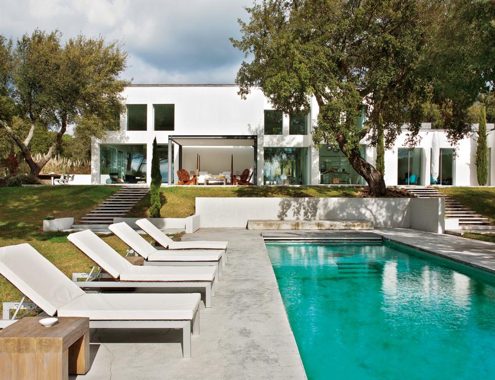 en el jardn emerge una piscina construida con cemento blanco las tumbonas de