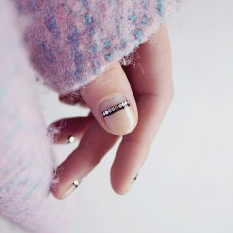 Nail Artist Frédérique Olthuis gave her negative nail a subtle shine. To get the look, paint a clear base coat and let dry. Add a thin, black stripe at the half moon. When tacky, add metallic flat sequins to the strip and seal it with a clear top coat. Design by @trnailart